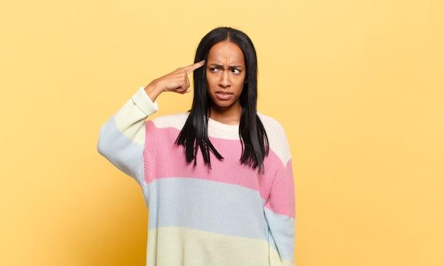 Jonge zwarte vrouw die zich verward en verbaasd voelt en laat zien dat je gek, gek of gek bent