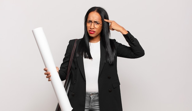 Jonge zwarte vrouw die zich verward en verbaasd voelt, laat zien dat je gek, gek of gek bent. architect concept