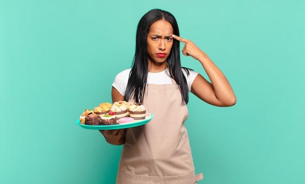 Jonge zwarte vrouw die zich verward en verbaasd voelt, laat zien dat je gek, gek of gek bent. bakkerij chef-kok concept