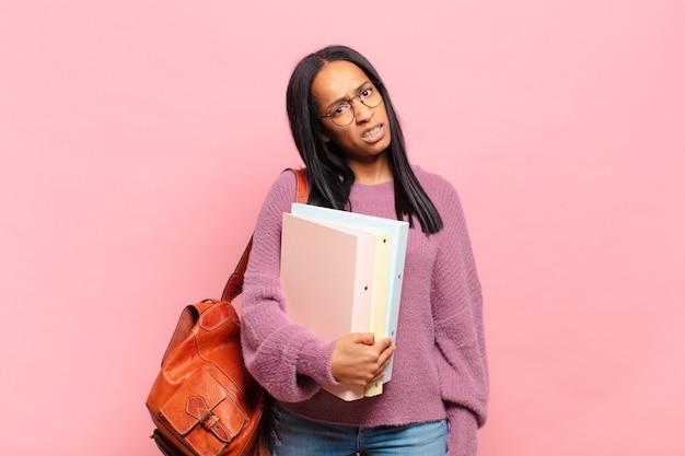 Jonge zwarte vrouw die zich verward en verward voelt, met een stomme, verbijsterde uitdrukking op zoek naar iets onverwachts. studentenconcept