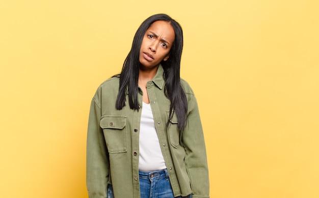 Jonge zwarte vrouw die zich verward en verward voelt, met een stomme, verbijsterde uitdrukking op zoek naar iets onverwachts