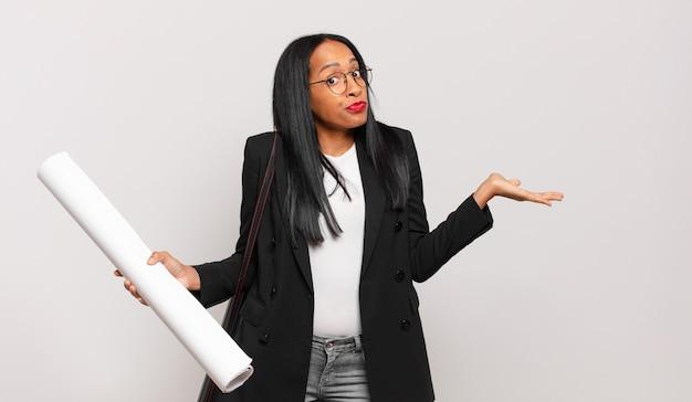 Jonge zwarte vrouw die zich verward en verward voelt, twijfelt, weegt of verschillende opties kiest met grappige uitdrukking. architect concept