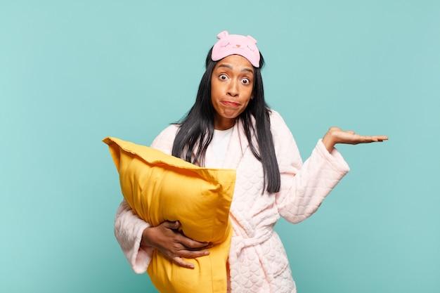 Jonge zwarte vrouw die zich verward en verward voelt, twijfelt, weegt of verschillende opties kiest met grappige uitdrukking. pyjama concept