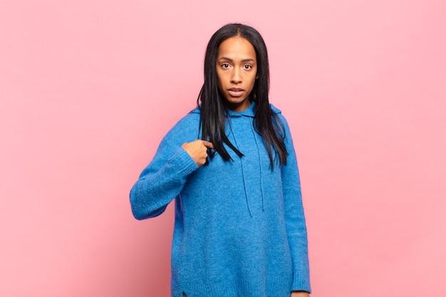 Jonge zwarte vrouw die zich verward, verbaasd en onzeker voelt, naar zichzelf wijst en zich afvraagt wie, ik?