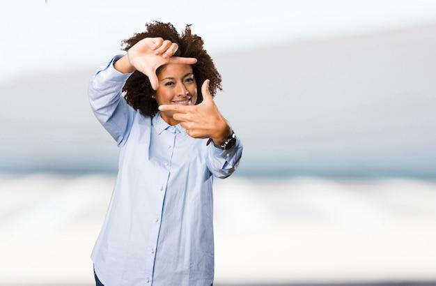 Jonge zwarte vrouw doet frame gebaar