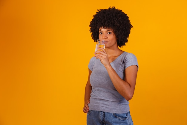 Jonge zwarte vrouw drinkwater op geel. jong meisje met glas water