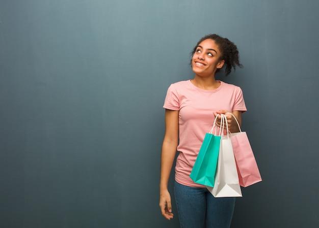Jonge zwarte vrouw droomt van het bereiken van doelen en doeleinden. ze houdt boodschappentassen vast.
