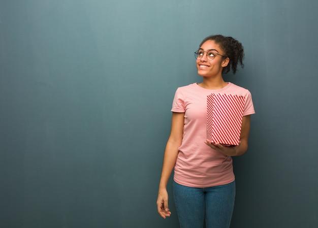 Jonge zwarte vrouw droomt van het bereiken van doelen en doeleinden. ze houdt een popcornsemmer.