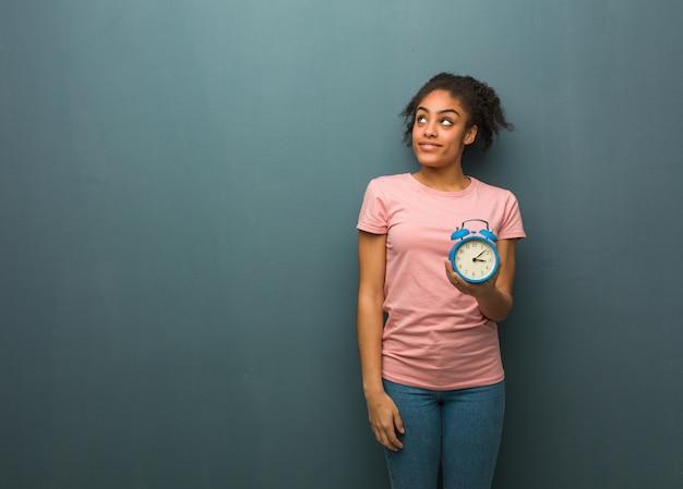 Jonge zwarte vrouw droomt van het bereiken van doelen en doeleinden. ze houdt een wekker.