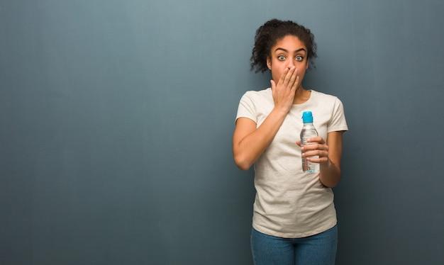 Jonge zwarte vrouw erg bang en bang verborgen. ze houdt een waterfles vast.