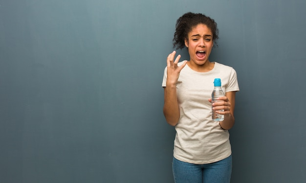 Jonge zwarte vrouw erg bang en bang. ze houdt een fles water vast.