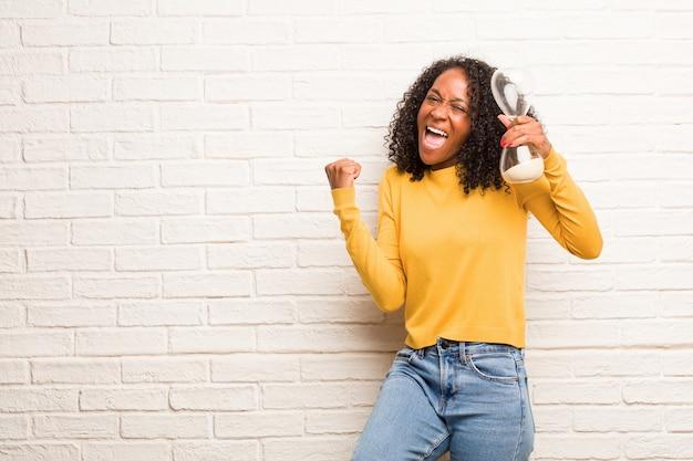 Jonge zwarte vrouw erg blij en opgewonden, het verhogen van de armen, het vieren van een overwinning of succes, het winnen van de loterij