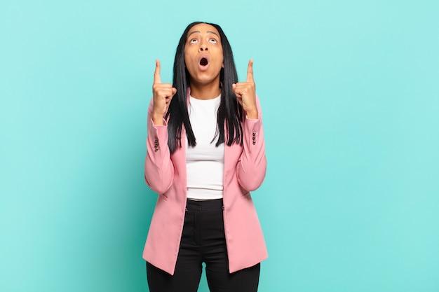 Jonge zwarte vrouw gevoel onder de indruk en met open mond naar boven wijzend met een geschokte en verbaasde blik. bedrijfsconcept