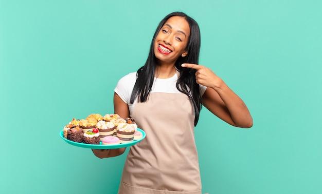 Jonge zwarte vrouw glimlachend vol vertrouwen wijzend naar eigen brede glimlach, positieve, ontspannen, tevreden houding. bakkerij chef-kok concept