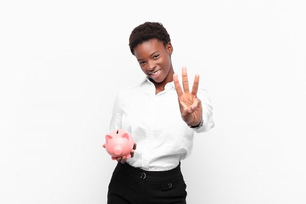 Jonge zwarte vrouw glimlacht en ziet er vriendelijk uit, toont nummer drie of derde met hand naar voren, aftellend met een spaarvarken