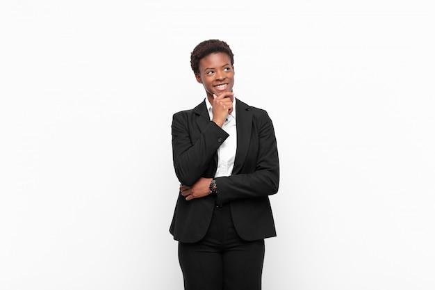 Jonge zwarte vrouw glimlacht met een gelukkige, zelfverzekerde uitdrukking met de hand op de kin, zich afvragend en naar de zijkant kijkend op een witte muur