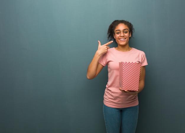 Jonge zwarte vrouw glimlacht, wijzend op mond. ze houdt een emmer popcorns vast.