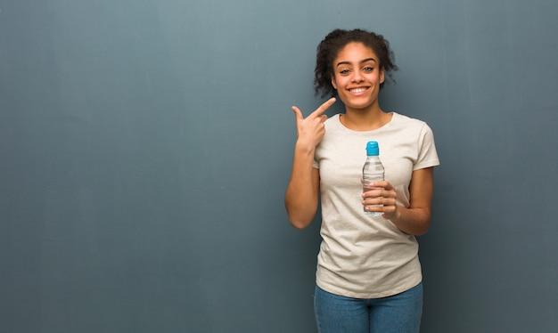 Jonge zwarte vrouw glimlacht, wijzend op mond. ze houdt een fles water vast.