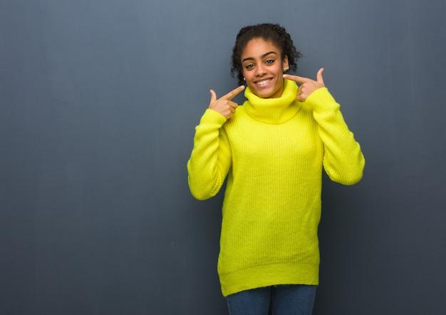 Jonge zwarte vrouw glimlacht, wijzend op mond