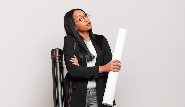 Jonge zwarte vrouw haalt haar schouders op, voelt zich verward en onzeker, twijfelt met gekruiste armen en kijkt verbaasd. architect concept