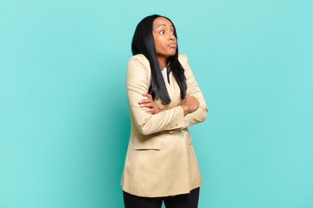 Jonge zwarte vrouw haalt haar schouders op, voelt zich verward en onzeker, twijfelt met gekruiste armen en kijkt verbaasd. bedrijfsconcept