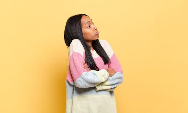 Jonge zwarte vrouw haalt haar schouders op, voelt zich verward en onzeker