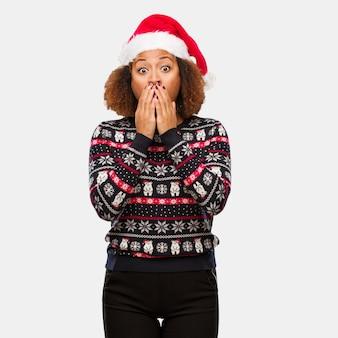 Jonge zwarte vrouw in een trendy kerst trui met afdrukken erg bang en bang verborgen