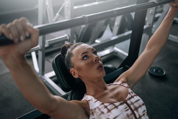 Jonge zwarte vrouw in trainingspak in de sportschool tilt de halter op