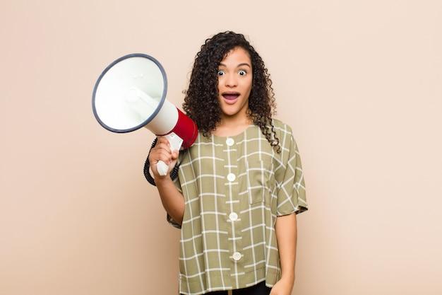 Jonge zwarte vrouw kijkt blij en aangenaam verrast, opgewonden met een gefascineerde en geschokte uitdrukking met een megafoon