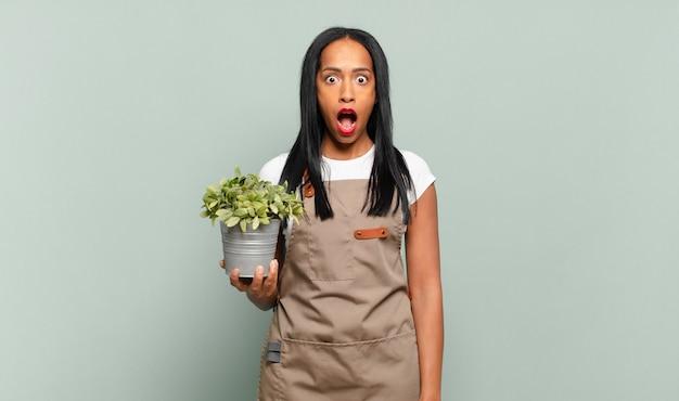 Jonge zwarte vrouw kijkt erg geschokt of verrast, starend met open mond en zegt wow. tuinman concept