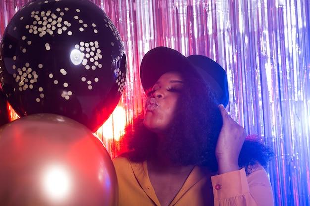 Jonge zwarte vrouw kijkt gelukkig terwijl ze tijd doorbrengt in de nachtclub. verjaardagsfeestje en nachtleven concept.