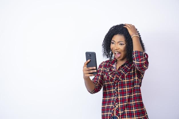 Jonge zwarte vrouw kijkt naar haar telefoon en ziet er verontrust en bezorgd uit