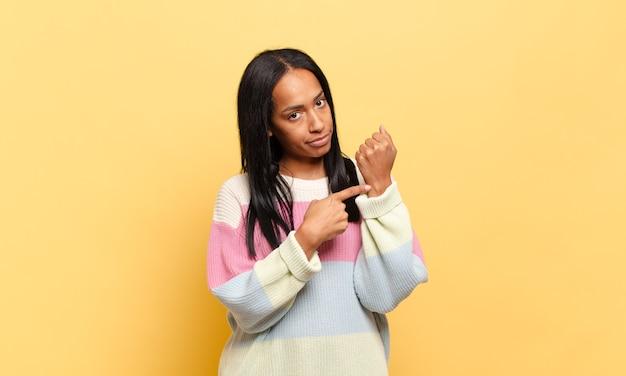 Jonge zwarte vrouw kijkt ongeduldig en boos, wijst op horloge, vraagt om stiptheid, wil op tijd zijn