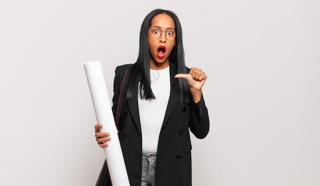 Jonge zwarte vrouw kijkt verbaasd in ongeloof, wijst naar een object aan de zijkant en zegt wow, ongelooflijk. architect concept