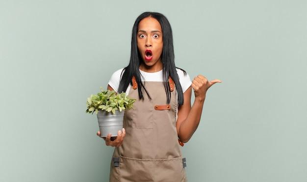 Jonge zwarte vrouw kijkt verbaasd in ongeloof, wijst naar een object aan de zijkant en zegt wow, ongelooflijk. tuinman concept