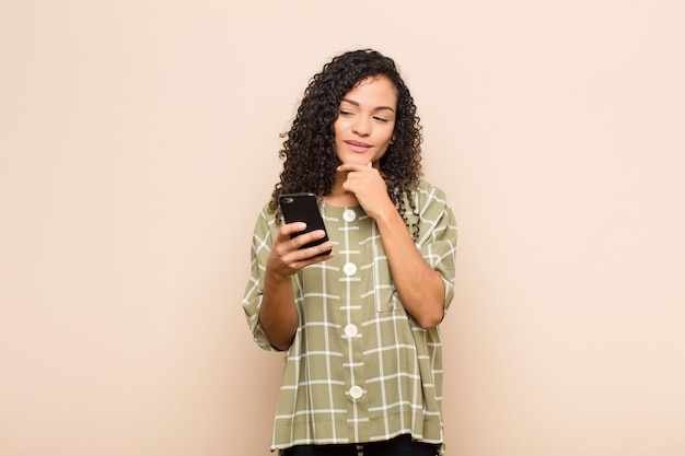 Jonge zwarte vrouw lachend met een gelukkige, zelfverzekerde uitdrukking met hand op de kin, zich afvragend en opzij kijkend met een smartphone