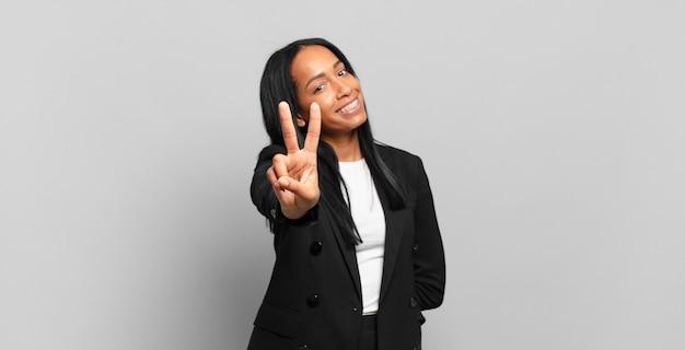 Jonge zwarte vrouw lacht en ziet er gelukkig, zorgeloos en positief uit, gebarend overwinning of vrede met één hand. bedrijfsconcept