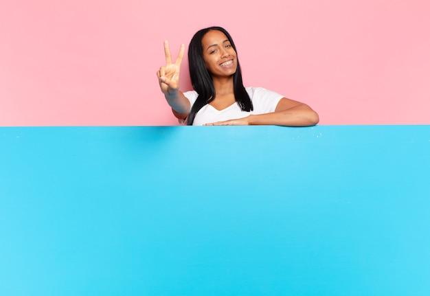 Jonge zwarte vrouw lacht en ziet er gelukkig, zorgeloos en positief uit, gebarend overwinning of vrede met één hand. kopieer ruimteconcept