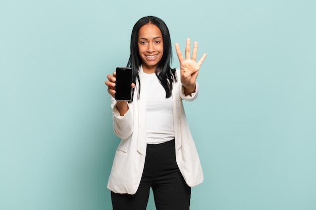 Jonge zwarte vrouw lacht en ziet er vriendelijk uit, nummer vier of vierde met hand naar voren, aftellend. slimme telefoon concept
