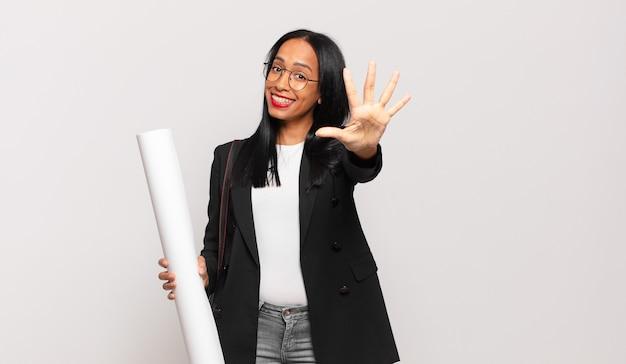 Jonge zwarte vrouw lacht en ziet er vriendelijk uit, nummer vijf of vijfde met hand naar voren, aftellend. architect concept