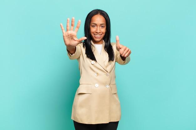 Jonge zwarte vrouw lacht en ziet er vriendelijk uit, nummer zes of zesde met hand naar voren, aftellend. bedrijfsconcept