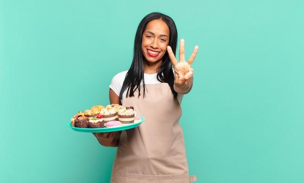 Jonge zwarte vrouw lacht en ziet er vriendelijk uit, toont nummer drie of derde met de hand naar voren, aftellend. bakkerij chef-kok concept