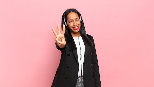 Jonge zwarte vrouw lacht en ziet er vriendelijk uit, toont nummer drie of derde met de hand naar voren, aftellend. telemarketing concept