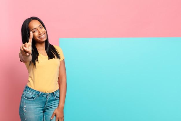 Jonge zwarte vrouw lacht en ziet er vriendelijk uit, toont nummer één of eerste met hand naar voren, aftellend. kopieer ruimteconcept