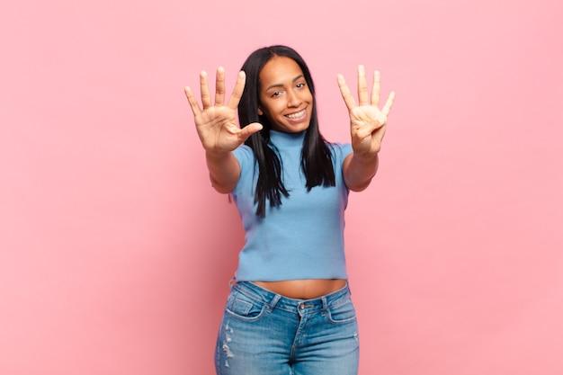 Jonge zwarte vrouw lacht en ziet er vriendelijk uit, toont nummer negen of negende met de hand naar voren, aftellend