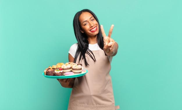 Jonge zwarte vrouw lacht en ziet er vriendelijk uit, toont nummer twee of seconde met de hand naar voren, aftellend. bakkerij chef-kok concept