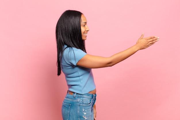 Jonge zwarte vrouw lacht, groet je en biedt een handdruk om een succesvolle deal te sluiten, samenwerkingsconcept