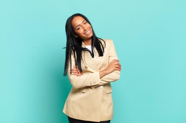 Jonge zwarte vrouw lacht vrolijk met gekruiste armen, met een ontspannen, positieve en tevreden pose. bedrijfsconcept