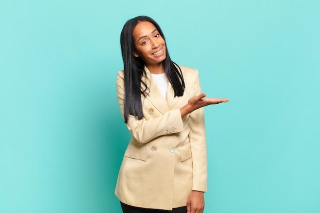 Jonge zwarte vrouw lacht vrolijk, voelt zich gelukkig en toont een concept in kopieerruimte met de palm van de hand. bedrijfsconcept
