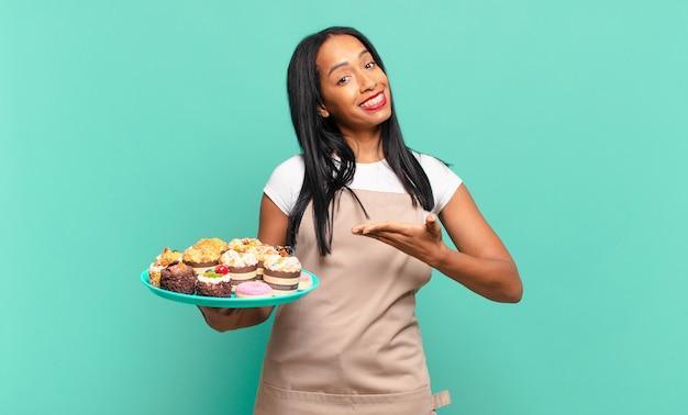 Jonge zwarte vrouw lacht vrolijk, voelt zich gelukkig en toont een concept in kopieerruimte met palm van hand. bakkerij chef-kok concept